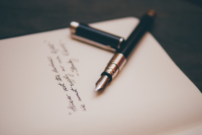 A fountain pen resting in the middle of writing